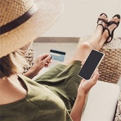 Relaxing woman wearing a hat while holding a credit card and phone